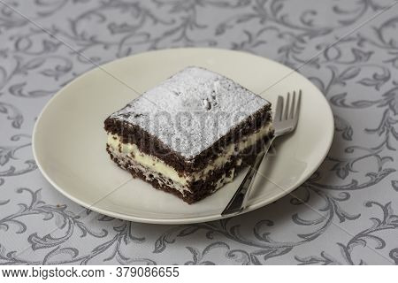 Dessert In A Square Shape Interlaced With Whipped Cream And Decorated With Sugar. The Dessert Is On