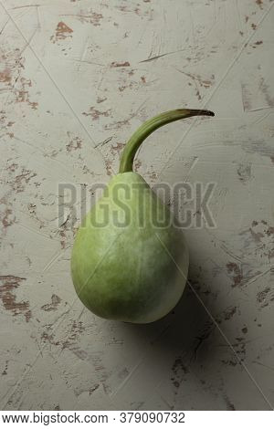 Green Bottle Gourd With Long Stem On White Background