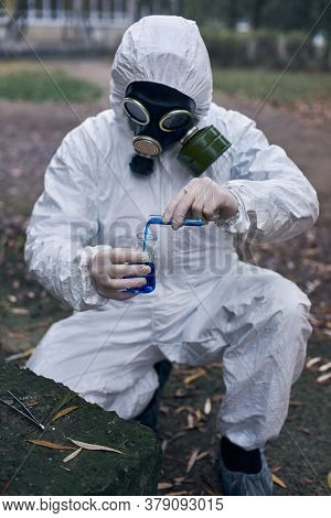 Ecologist In Protective Suit And A Gas Mask, Working In Exclusion Zone, Making Tests Using Laborator