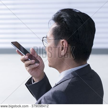 Chinese Businessman Using Cellphone To Leave Voice Message. Closeup, Head Shot.