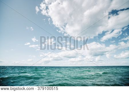 Turquoise Water In A Cold Nordic Sea Under A Blue Sky With White Clouds