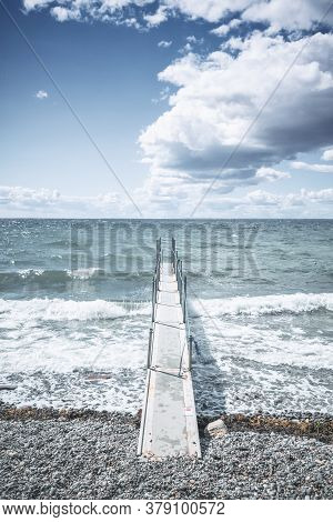 Small Pier At A Cold Sea With Waves Coming In On The Pebble Beach