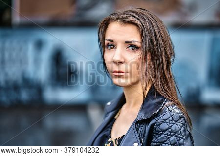 Girl Of Brunette  In A Black Leather Jacket  On A Walk In  City On A Cloudy Summer Evening.  Closeup