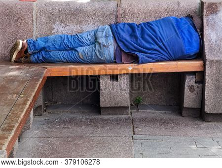 Homeless Man Sleeping Rough On A Wooden Park Bench During The Day. A Symbol Of The Growing Problems