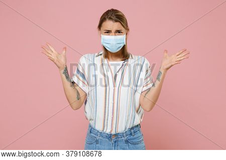 Irritated Young Blonde Woman Girl In Casual Striped Shirt Sterile Face Mask Isolated On Pink Wall Ba