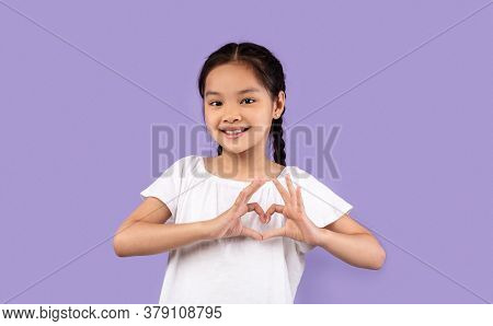 Love And Kindness. Little Asian Girl Gesturing Heart Shape Smiling To Camera Posing On Purple Studio