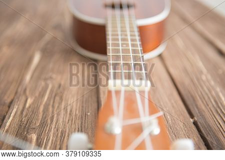 Photo Depicts Musical Instrument Ukulele Guitar On Wooden Table