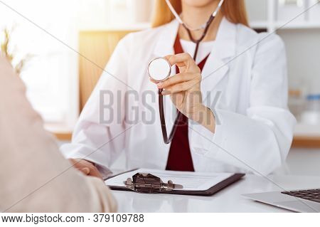 Unknown Woman-doctor With A Stethoscope In The Hands At Sunny Room, Close-up Of Hands. Medicine Conc