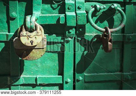 Old Metal Padlock On A Green Wooden Door Of Barn