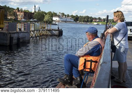 A Ferry Worker Is Waiting For The Ferry To Moor And Dock. The Passenger Is Waiting For The End Of Th