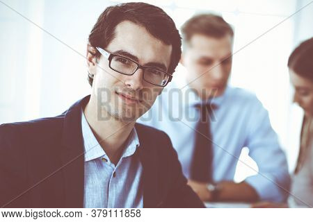 Group Of Business People Discussing Questions At Meeting In Modern Office. Headshot Of Businessman A