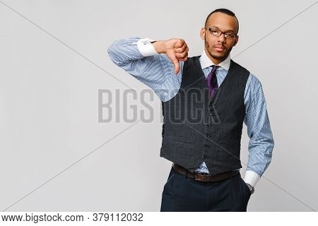 Young Black Businessman With A Dissenting Serious Dislike Expression With Thumbs Down In Disapproval