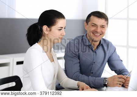 Cheerful Smiling Businessman And Woman Working With Computer In Modern Office. Headshot At Meeting O
