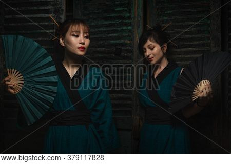 Attractive two geishas in dark turquoise kimono holding hand fan against dark wooden shutters background.