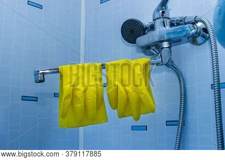Yellow Rubber Gloves. Gloves Are Hanging On The Tap In The Bathroom. House Cleaning. Bathroom Cleani