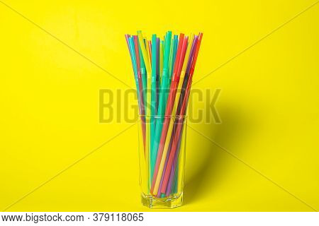 Colored Cocktail Tubes In A Glass. Holiday Concept. Photo On A Yellow Background.