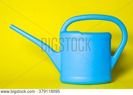 Blue Watering Can On A Yellow Background. The Watering Can Has A Place For An Inscription Or Logo. G