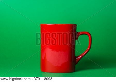 Red Mug On A Green Background. The Mug Has A Place For An Inscription Or A Logotype.