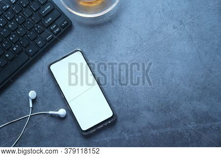 Smart Phone With Empty Screen, Headphone And Tea On Black Background
