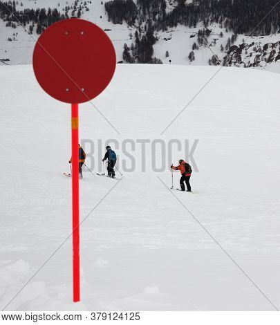 Red Marker On Off-piste Snowy Slope For Freeriding In High Winter Mountains. Ski Area Mottolino Fun