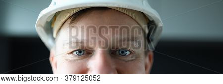 Close-up Of Cheerful Worker Face. Macro Shot Of Foreman In Protective White Helmet Posing On Camera