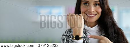 Close-up Of Smiling Beautiful Businesswoman Pointing At Wristwatch. Pretty Young Brunette Woman In L