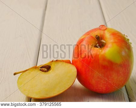 An Apple, On A White Wooden Background. Close-up. Dietary Nutrition.