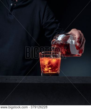 Bartender Pouring Whiskey Into Glass At Bar Counter. Alcoholic Drink Pouring From A Bottle Into A Fr