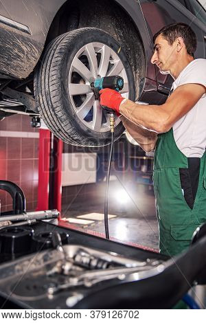 Mechanic In Uniform Is Working In Auto Service With Lifted Vehicle