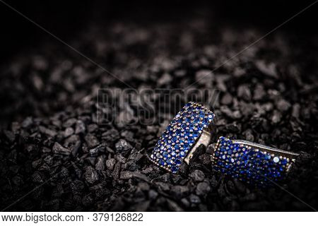 Couple Of Woman Earrings Close Up On Coal Texture With Space For Your Text