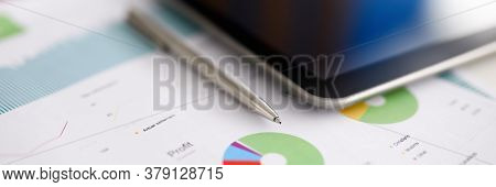 Silver Pen Adn Digital Tablet Pc Lie On Office Table Against Business Chart Background Closeup. Indi