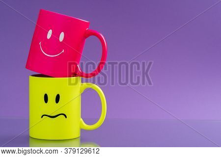 Two mugs with  happy and sad emotions on the background. Concept, Coffee Mugs with sadness and kindness happy face. Happy and sadness smiles mood