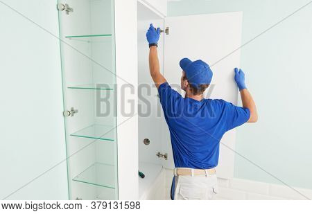 Installer contractor at furniture assembling work. Worker installing bathroom cupboard.