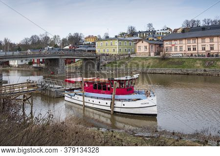April 17, 2019 Porvoo, Finland, Cityscape. Old Houses By The River In With A Pleasure Boat