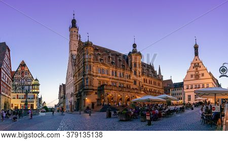 People Enjoy A Beautiful Summer Evening In The Street Cafes In The Market Square Of Rothenburg