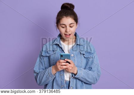 Portrait Of Astonished Woman With Modern Smart Phone In Hands, Dresses Stylish Outfit, Looking At Sc