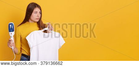 Young Woman Steaming Her Clothes At Home, Holding Steam Iron And White T Shirt On Hangers In Hands,