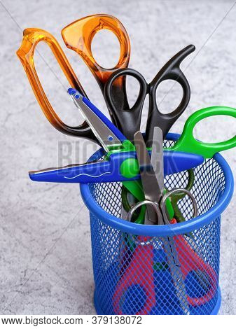 Scissors Of Different Sizes And For Different Jobs Are In A Mesh Container. Children's Scissors With