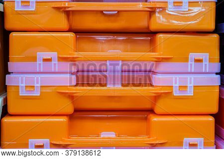 Plastic Orange Tool Boxes On Store Shelves. Stack Of Organizers Close-up.