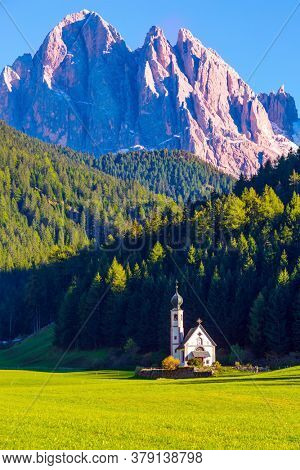 Small white church with a bell among green lawns on the sunset. The gorgeous village Santa Maddalena in the Val di Funes Valley. Tyrol, Italy. The concept of ecological and photo tourism