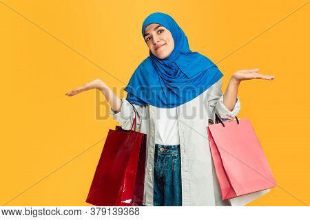 Emotional. Young Muslim Woman With Colorful Shopping Packages On Yellow Studio Background. Stylish,