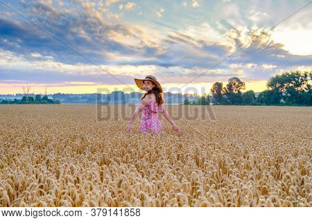 Young Cheerful Woman In Straw Hat In The Middle Of Wheat Field With Outstretched Arms Turn Around To