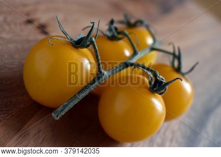 Fresh Yellow Organic Cherry Tomatoes With Vine On A Wooden Chopping Board Background. Close Up Low A