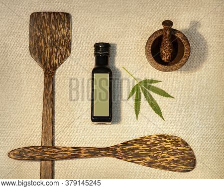 Medicinal Hemp Oil Extract Surrounded By Wooden Spoons And A Mortar With A Pestle