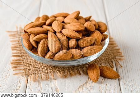 Tasty Raw Almonds In A Glass Saucer On A White Wood Table. Unroasted Nuts As Antioxidant And Protein