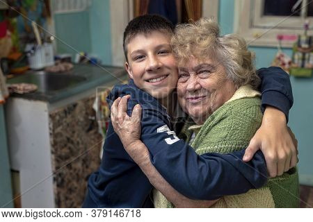 Happy, Smiling Grandson Hugs His Grandmother In The Kitchen At Home. Happy Family Relationships, Lov