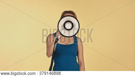 Pretty girl shouting into megaphone on yellow copy space