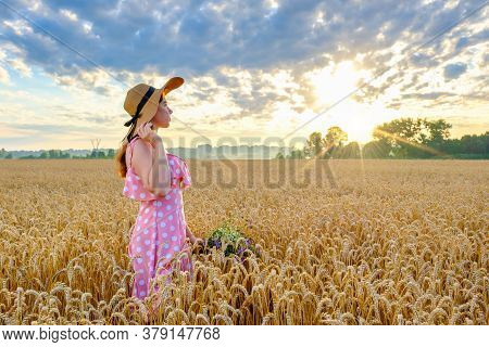 Pretty Young Girl With Long Hair Looks To The Sun And Holds A Wild Flower Bouquet In Wheat Field At