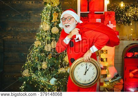 Happy New Year. Christmas Time. Its Almost Twelve Clock. Santa Make Funny Face And Holding Clock Sho