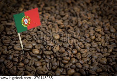 Portugal Flag Sticking In Roasted Coffee Beans. The Concept Of Export And Import Of Coffee
